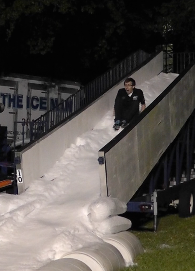 Osprey Productions Director Brent Fine takes a turn on the ice slide at Winterfest.