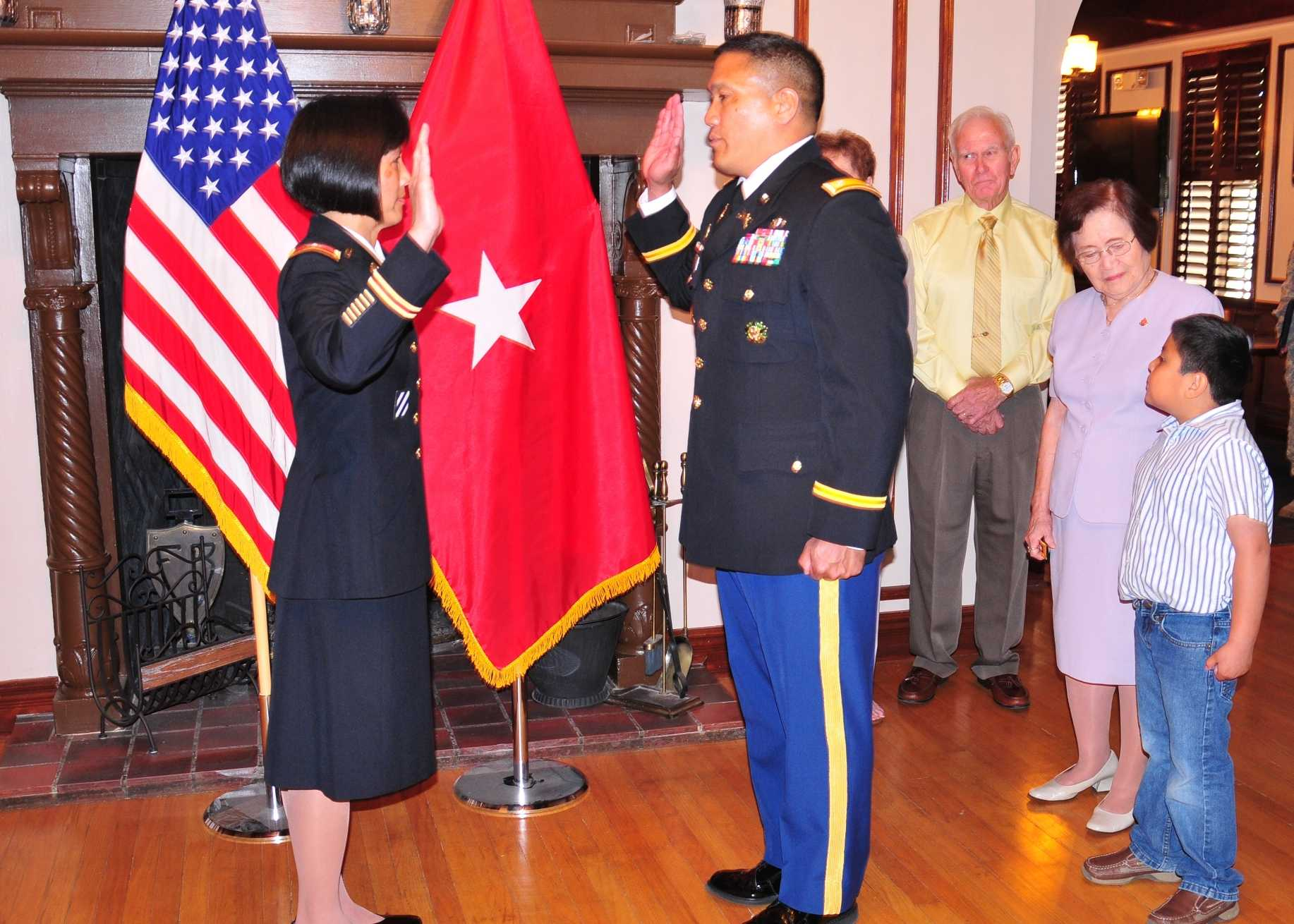 Col. Leslie Caballero, left, is sworn in to her new rank by her brother, Lt. Col. Leo Caballero, who read her oath of office while family and friends watched nearby. Photo by Lt. Col. Deanna Bague