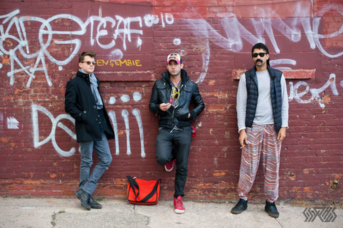 The members of Sisyphus standing in front of a graffiti'ed brick wall. Photo courtesy Facebook.