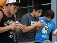 From left to right, Mickey Nguyen, Dustin Go and David Ha try and scarf down their burritos as fast as they can at the burrito eating contest that took place today at noon at Market Day. Photo by Joshua Brangenberg
