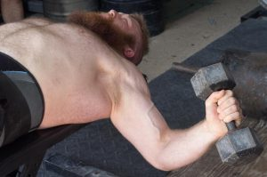 Clayton stretches his chest muscles by lifting 25 lbs. weights above his torso.Photo by Tyler Voorthuijsen
