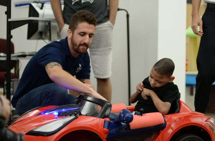 Student shows Maddex, a five-year-old with cerebral palsy, how to use the joystick in order to drive the car.  (Courtesy of Joanna Norris)