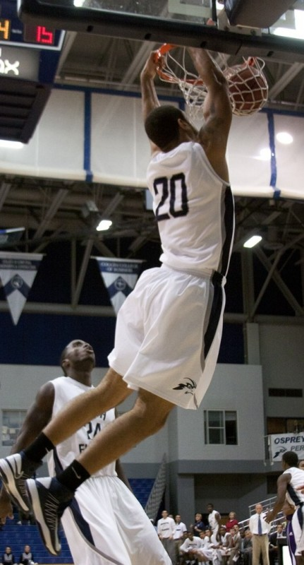 Senior forward Andy Diaz (20), who has averaged 7 ppg through three games, flushes a dunk against Edward Waters College.