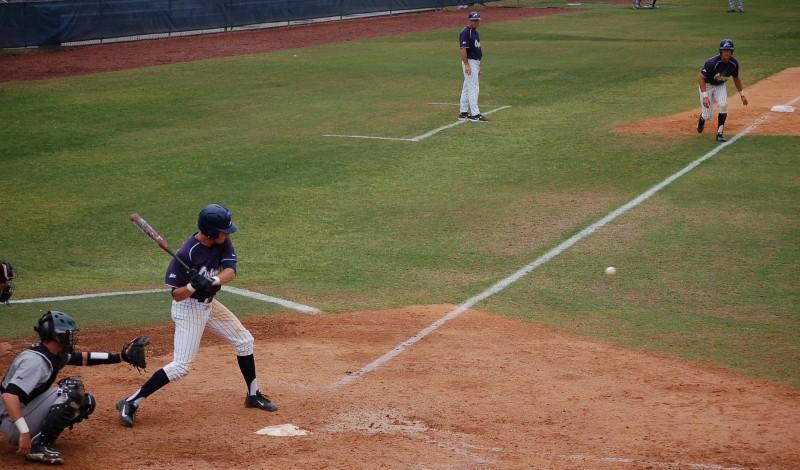 Photo Credit: Travis Gibson Drew Weeks takes a cut against NKU while Tyler Marincov waits on third base.