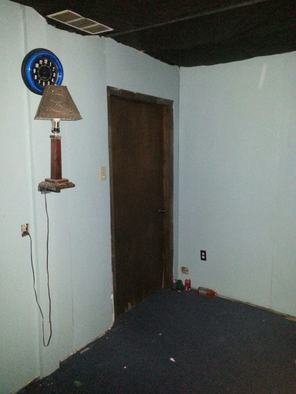 The room with white bare walls, a blue clock and creepy lamp