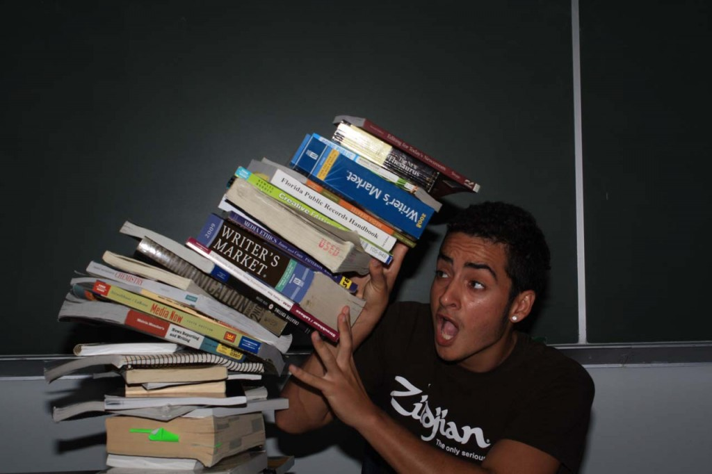 Joshua Rodrigez, communications junior, gets crushed by textbooks. Many students  use alternative methods to buying textbooks such as renting, sharing, or avoiding them altogether. Photo by Zach Schoenheide