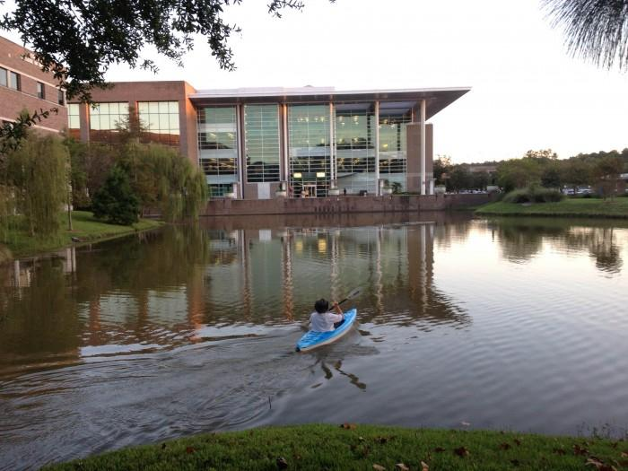 Dr. Lunberry crosses the library pond in a kayak to rearrange the lettering from Emily Dickinson's poem. Photo by Lydia Moneir