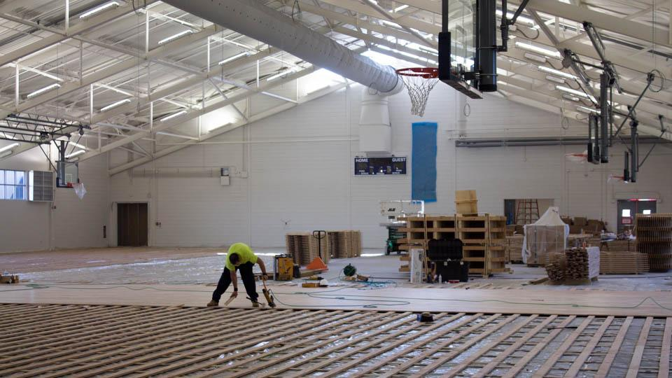 A construction worker installs flooring in the new Field House facility.  Photo by Michael Herrera