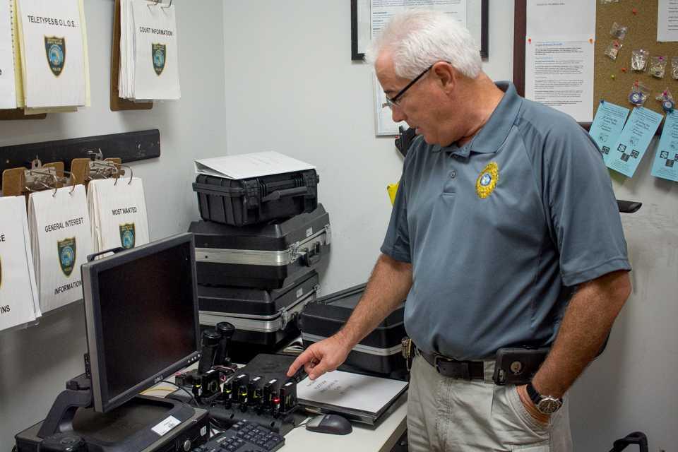 Police Chief Frank Mackesy examines UNFPD body cam gear. <br><i>Photo by Michael Herrera</i>
