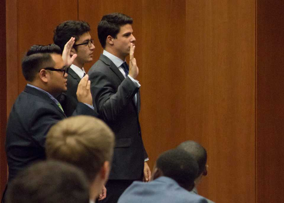 Jordan Wilson, Justin Dato, and Glehn Von Loh swearing in to their student government positions.  <i>Photo by Michael Herrera</i>