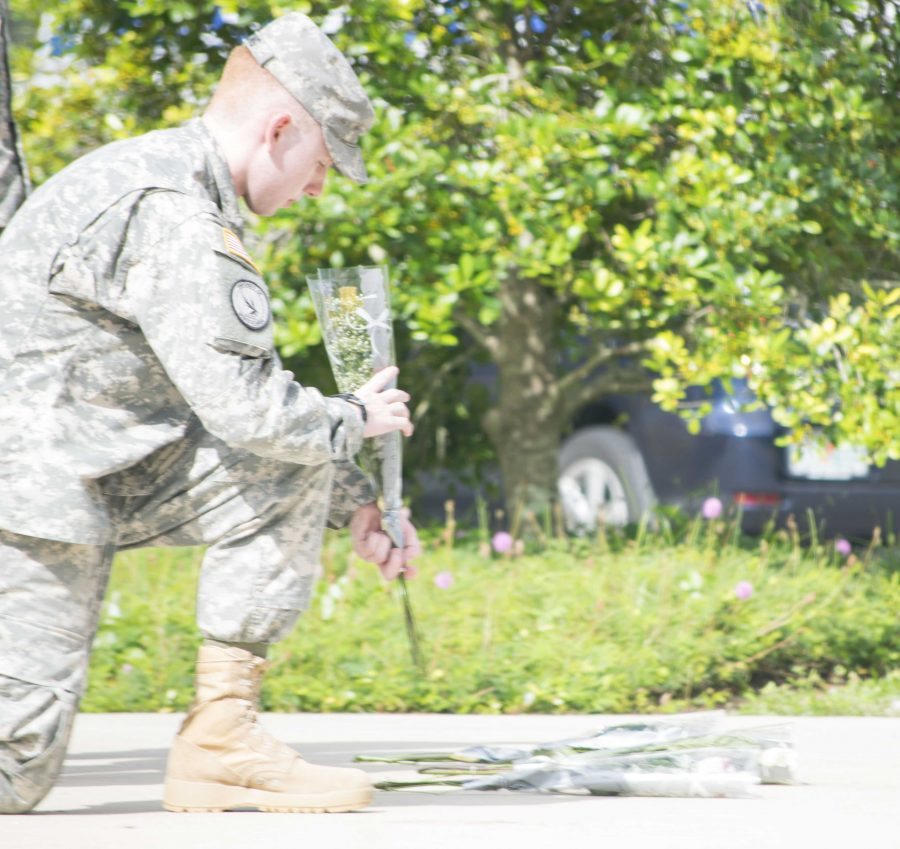 Cadet Cpl. Adam Young, criminal justice sophomore, lays down a rose beneath the United States flag.   Photo by Christian Ayers