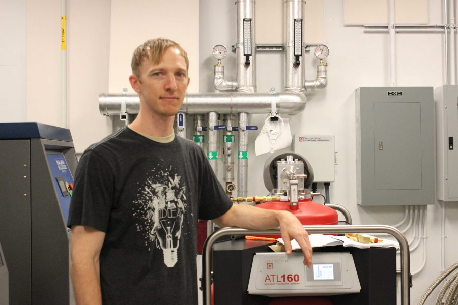 Senior physics major Thomas Olejiczak with UNF's helium liquefier. Photo by Jack Drain