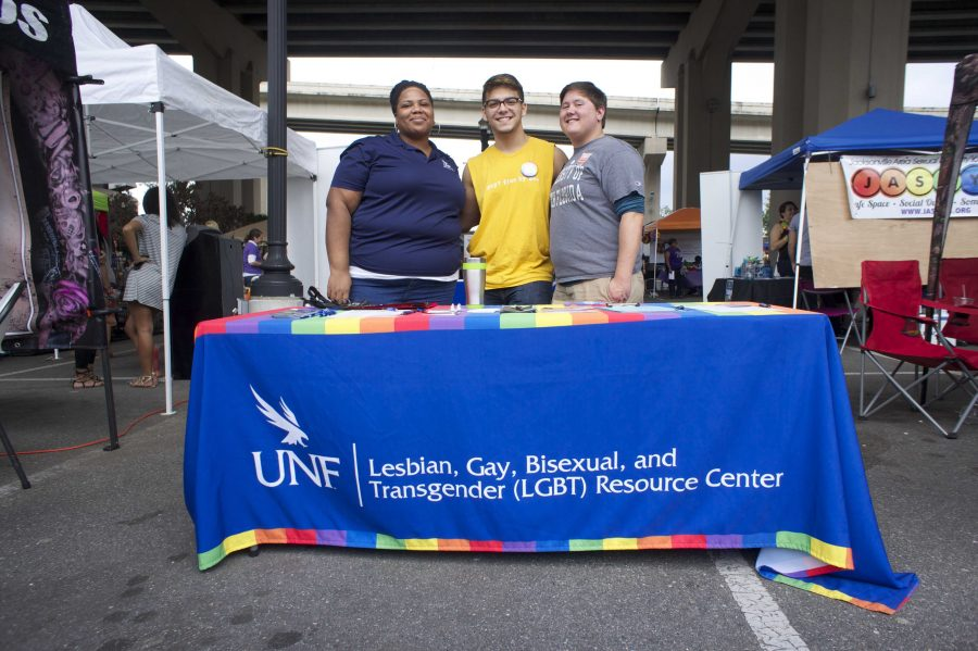 Junior psychology major Josef Kim (middle) stopped by the LGBT Center tent with Jake Moore, program director of the center. Kim is a frequent visitor to the center on campus, spreads the word about their upcoming events and coordinates other events for the center. Photo by Rachel Cazares