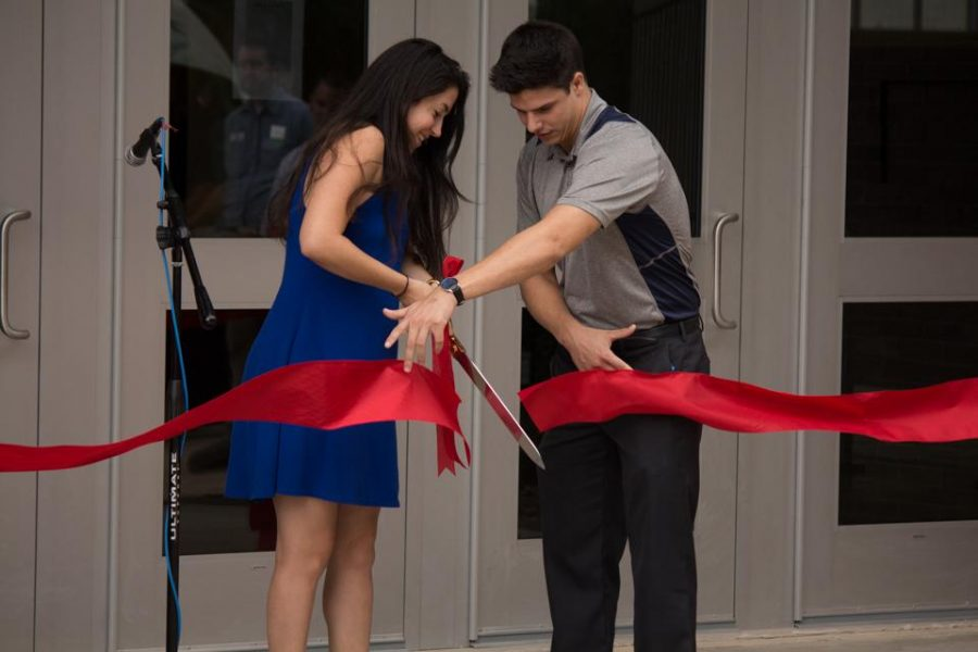 Student Government President Hailey Guerra cuts the ribbon while SG Vice President Jordan Wilson dodges the sharp blades. Photo by Michael Herrera