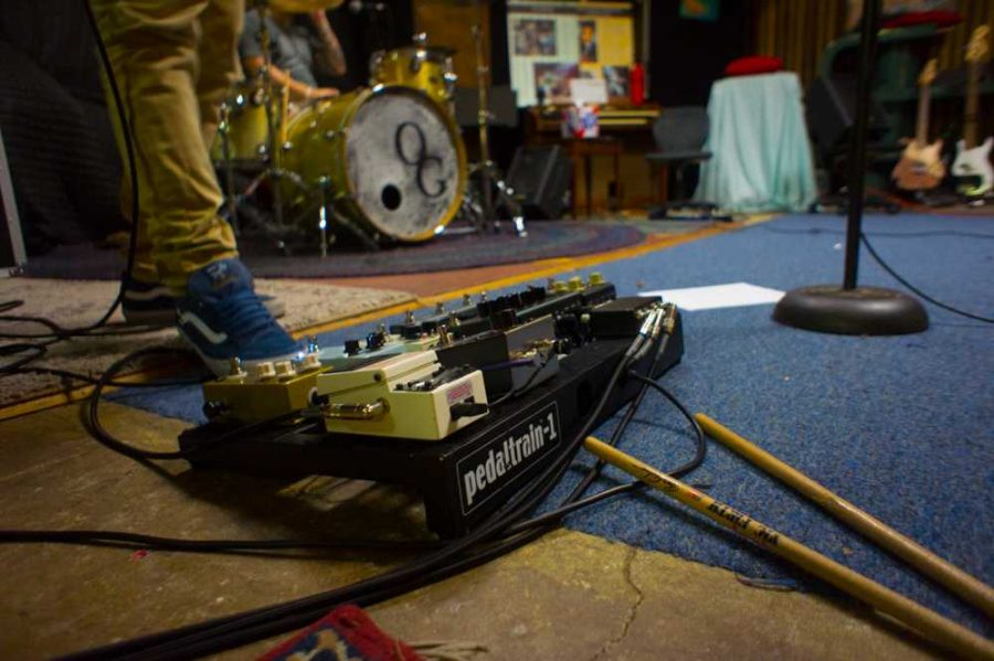Guitarist Josh Ivey tests out his new distortion pedals he got out of trading with a friend. Photo by Rachel Cazares