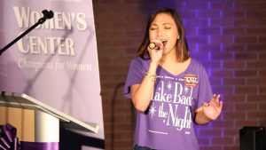 """Jenniviev Gubat, a member of Alpha Chi Omega, sang """"Fight Song,"""" by Rachel Platten. Gubat replaced some of the lyrics with """"take back the night song"""" in honor of the event. Photo by Michael Herrera"""