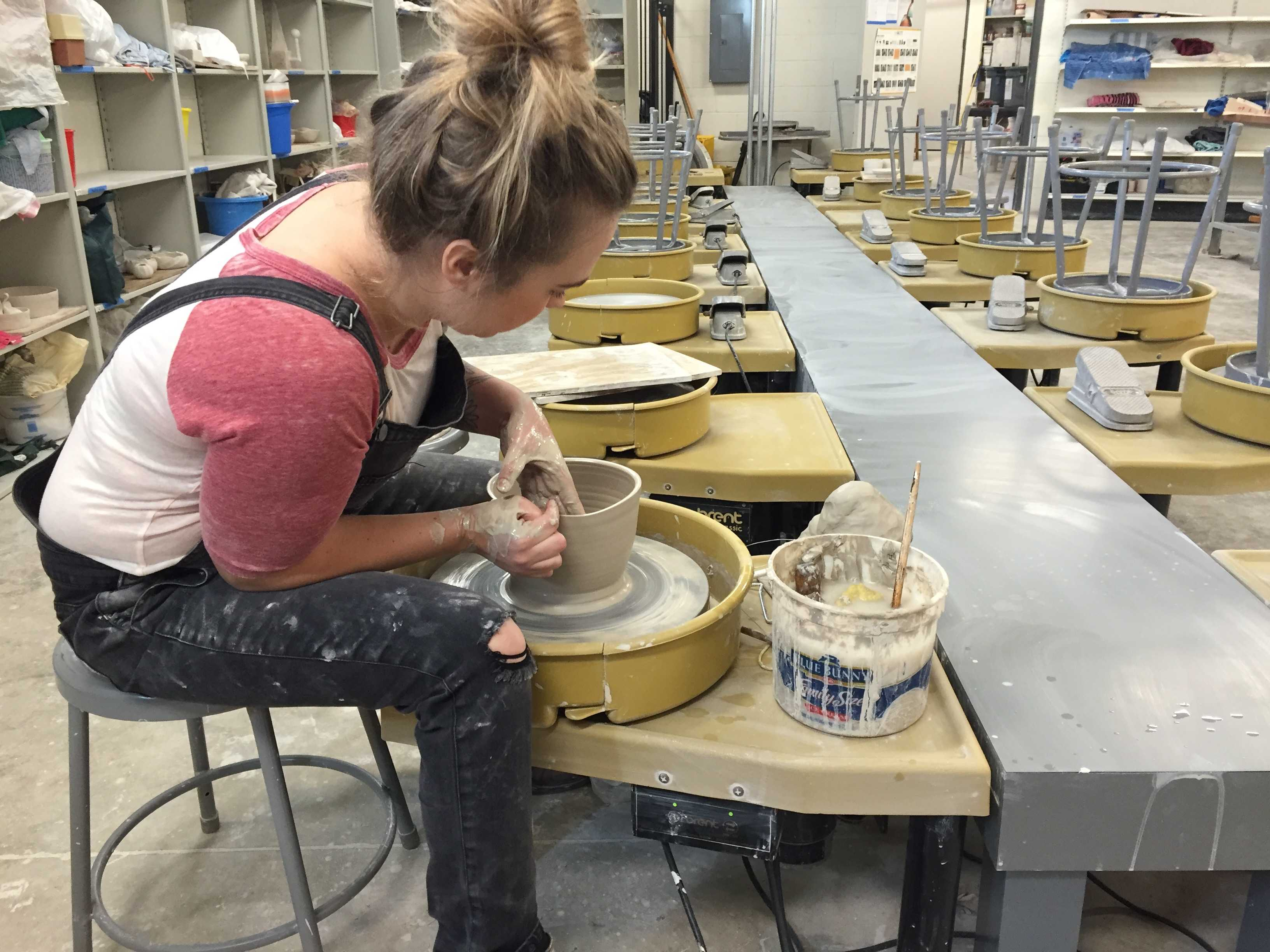 Tanner works on a piece in the ceramics studio on campus. Photo by Tiffany Salameh