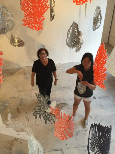 Goloborotko (left) viewing her work from above with UNF fine art student Camille Modesto.