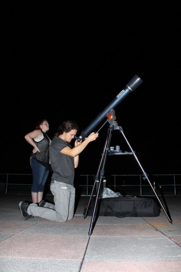 Astrophysics Professor Dr. Hewitt and Astrophysics Student set up the main telescope for attendees to view nearby planets and stars. Photo by Ashley Pace