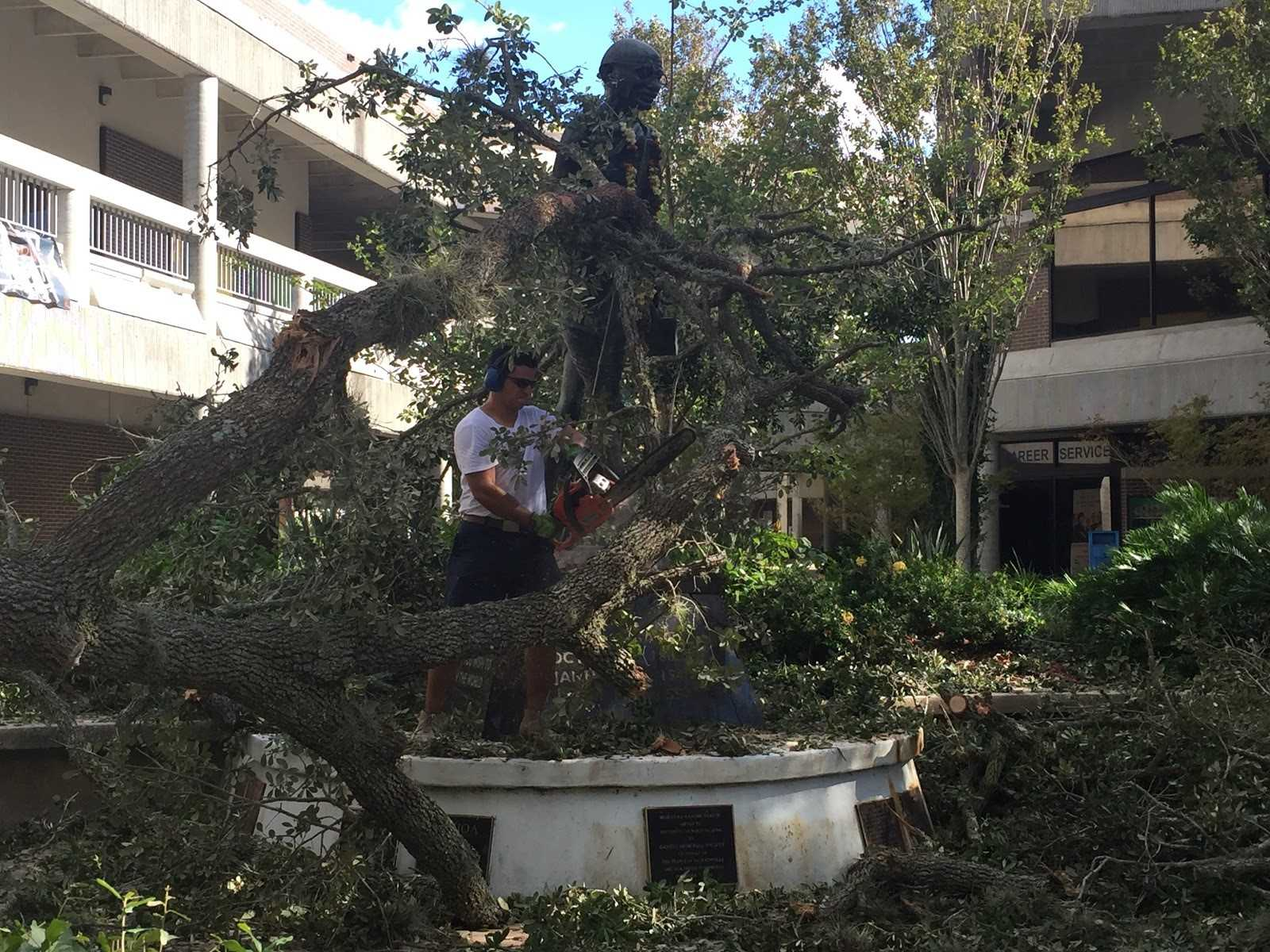 UNF alumni Juan Carlos Villatoro came to campus to help clear debris from the Ghandi statue after Hurricane Matthew. <i>Photo by Pierce Turner</i>