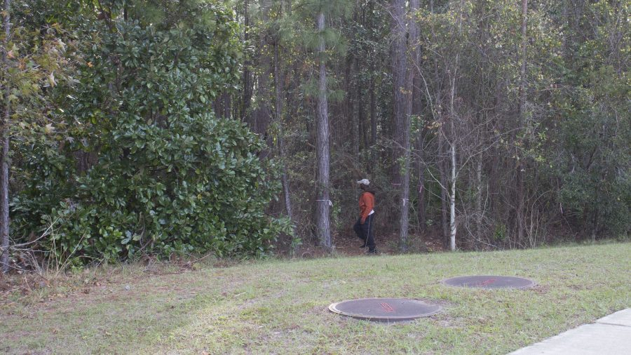 An officer entered the woods on Tuesday to search for Louissaint. <i>Photo by Pierce Turner</i>