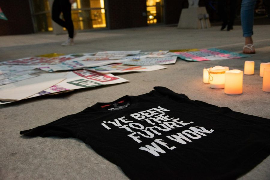 Preparation for vigil with lit candles, signs, and inspirational t-shirt.