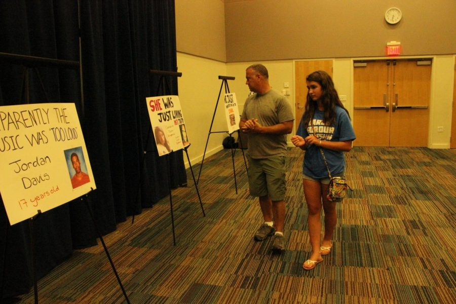 Town Hall attendees looking at posters of people who fell victim to gun violence.