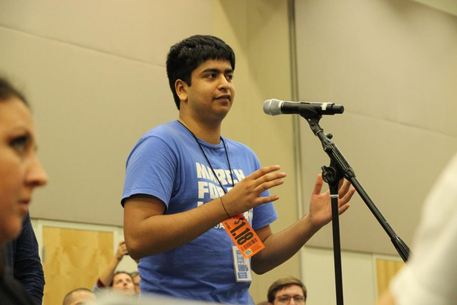 Young adult asking a question to the panelists.