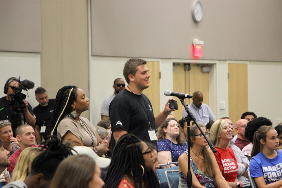 Staff member of the Utah Gun Exchange asking the panelists a question.