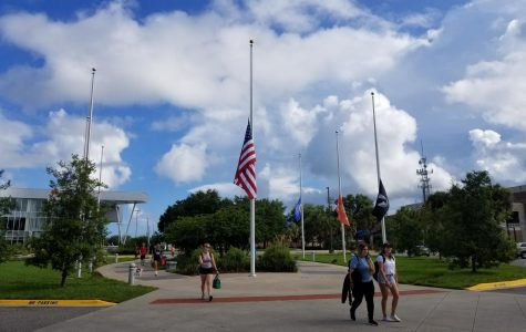 Students walk by UNF's flags held at half-staff. Photo by Sam Chaney.