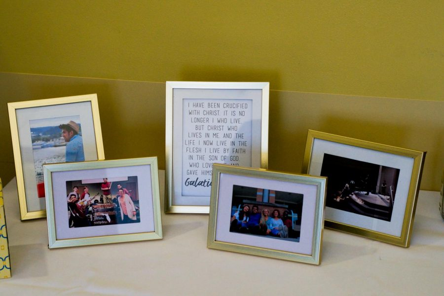 Framed pictures of Greg Yutuc with friends and family displayed on table, along with framed bible verse.