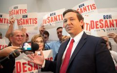 Ron DeSantis answers questions for the press with his supporters by his side.