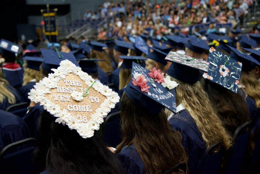 Graduates displaying their customized caps.