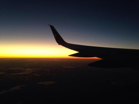 The wing of a plane in front of a sunset.