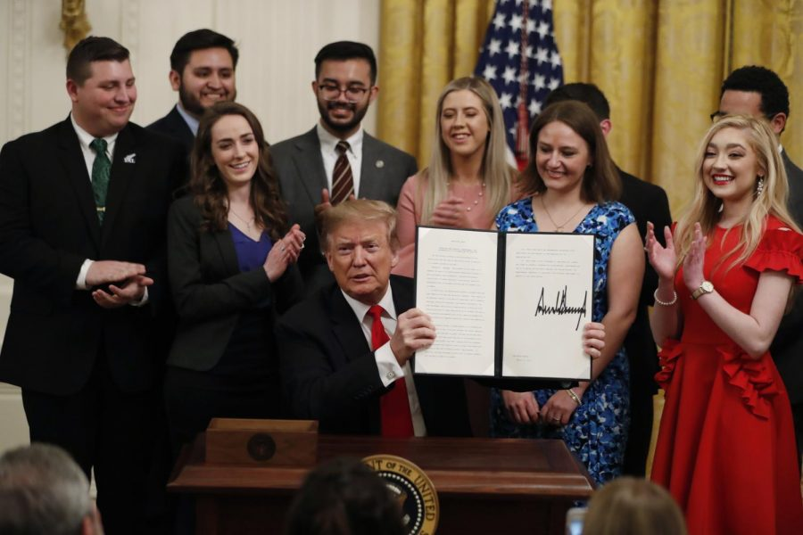 President Donald Trump holds up an executive order requiring colleges to certify that their policies support free speech as a condition of receiving federal research grants, after signing, Thursday March 21, 2019, in the East Room of the White House in Washington.