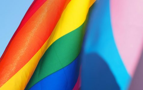 LGBTQ+ flags against blue sky.