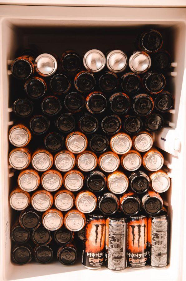 Multiple cans of Monster energy drinks in a fridge.