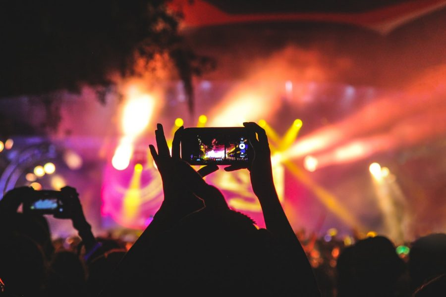 Person holding their phone up to take pictures at a concert