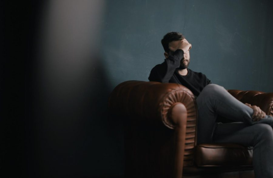 man sitting on couch against wall, looking sad