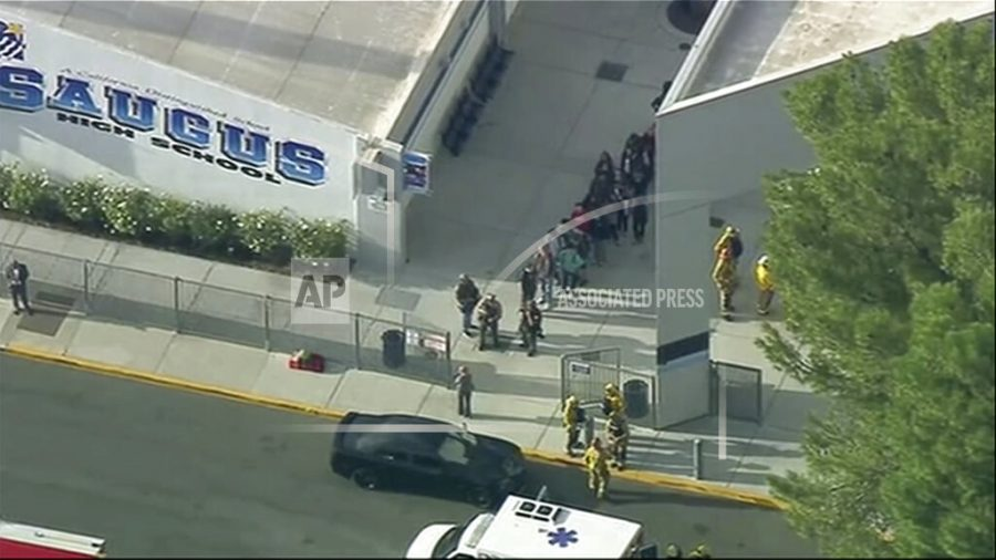 People are lead out of Saugus High School after reports of a shooting on Thursday, Nov. 14, 2019 in Santa Clarita, Calif.  The Los Angeles County Sheriff's Department says on Twitter that deputies are responding to the high school about 30 miles (48 kilometers) northwest of downtown Los Angeles. The sheriff's office says a male suspect in black clothing was seen at the school.  (KTTV-TV via AP)