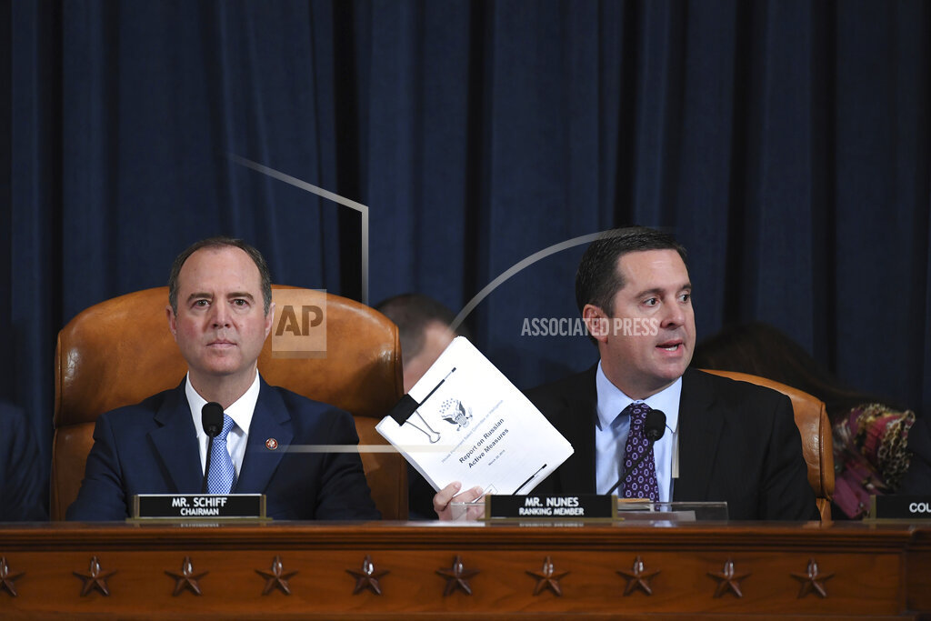 Rep. Devin Nunes, R-Calif., right, the ranking member of the House Intelligence Committee, joined by Chairman Adam Schiff, D-Calif., left, holds up a document he is submitting as the panel prepares to listen to former White House national security aide Fiona Hill, and David Holmes, a U.S. diplomat in Ukraine, on Capitol Hill in Washington, Thursday, Nov. 21, 2019, during a public impeachment hearing of President Donald Trump's efforts to tie U.S. aid for Ukraine to investigations of his political opponents. (Matt McClain/Pool Photo via AP)