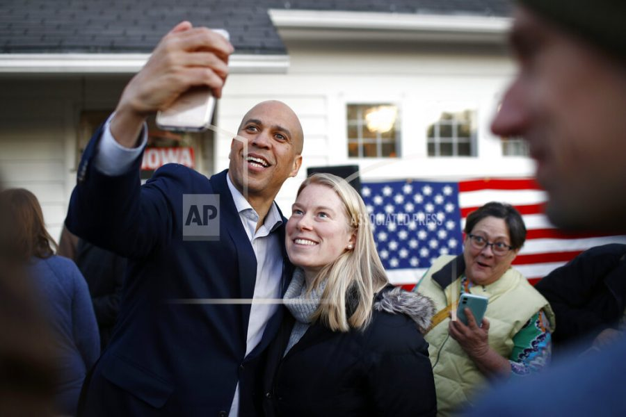"""Democratic presidential candidate Sen. Cory Booker, D-N.J., poses for a selfie with an attendee after speaking at a campaign event at the home of Polk County Democratic Chair Sean Bagniewski, Tuesday, Jan. 7, 2020, in Des Moines, Iowa. Booker said a looming impeachment trial and other pressing issues in Washington could deal a """"big, big blow"""" to his Democratic presidential campaign by keeping him away from Iowa in the final weeks before the Feb. 3 caucuses. (AP Photo/Patrick Semansky)"""