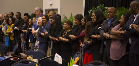 "Rev. Webb demonstrates the ""love chain"" with attendees. Photo credit Christian Ayers."