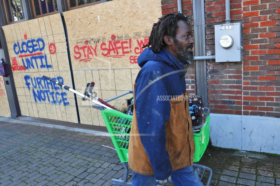 FILE - In this Tuesday, March 31, 2020 file photo, Vincent Amos, who identified himself as homeless, pulls a shopping cart with his belongings amid businesses closed by concerns of the COVID-19 coronavirus in the Deep Ellum section of Dallas. Amos said his shelter in place routine includes walking the area looking for work cleaning windows. (AP Photo/LM Otero)