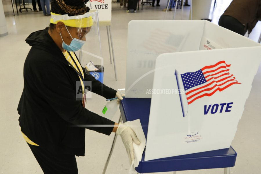 Board of elections worker Valerie Tyree cleans an election booth after a person voted in the state's primary election at the Cuyahoga County Board of Elections, Tuesday, April 28, 2020, in Cleveland. The first major test of an almost completely vote-by-mail election during a pandemic is unfolding Tuesday in Ohio, offering lessons to other states about how to conduct one of the most basic acts of democracy amid a health crisis. (AP Photo/Tony Dejak)