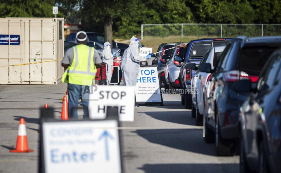 FILE - In this May 15, 2020, file photo, Walmart employees conduct COVID-19 testing for pre-registered individuals in the parking lot of the Ramsey Street Walmart in Fayetteville, N.C. Coronavirus cases are rising in nearly half the U.S. states, as states are rolling back lockdowns. (Julia Wall/The News & Observer via AP, File)