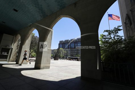 FILE - In this May 20, 2020 file photo a runner passes through an arch on the campus of Boston University, in Boston. COVID-19 has disrupted the plans of an estimated 3 million returning college students. Due to the pandemic's financial and psychological stressors, some students are debating whether they should sit out this fall. While taking time out from school during the pandemic might seem like a safe choice, it could have lasting consequences.  (AP Photo/Steven Senne, File)