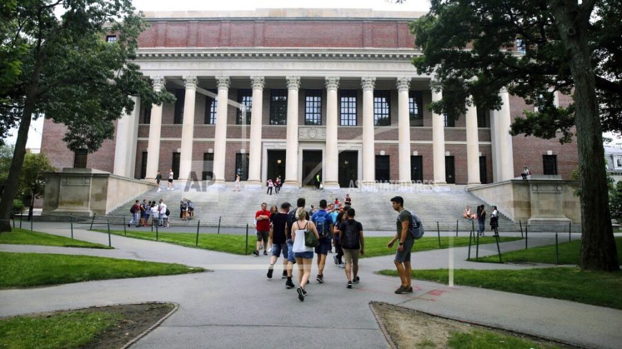 FILE - In this Aug. 13, 2019 file photo, students walk near the Widener Library in Harvard Yard at Harvard University in Cambridge, Mass. The Ivy League school announced Monday, July 6, 2020, that as the coronavirus pandemic continues its freshman class will be invited to live on campus this fall, while most other undergraduates will be required learn remotely from home. (AP Photo/Charles Krupa, File)