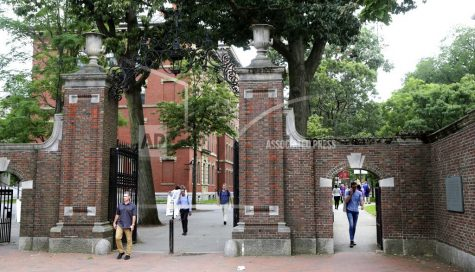 FILE - In this Aug. 13, 2019, file photo, pedestrians walk through the gates of Harvard Yard at Harvard University in Cambridge, Mass. Harvard and the Massachusetts Institute of Technology filed a federal lawsuit Wednesday, July 8, 2020, challenging the Trump administration
