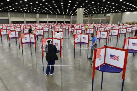 FILE - In this June 23, 2020, file photo voting stations are set up in the South Wing of the Kentucky Exposition Center for voters to cast their ballot in the Kentucky primary in Louisville, Ky. The November election is coming with a big price tag as America faces the coronavirus pandemic. The demand for mail-in ballots is surging, election workers are in need of training and polling booths might have to be outfitted with protective shields. (AP Photo/Timothy D. Easley, File)